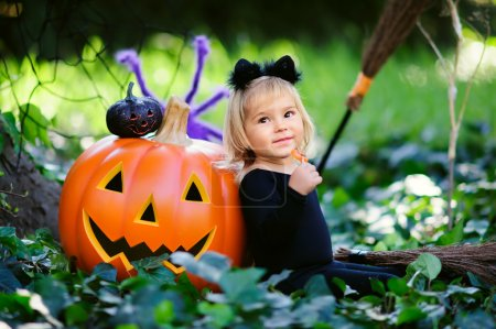 little girl in halloween costume with candy and jack pumpkin