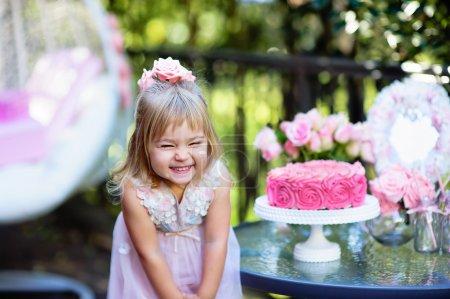 Foto de Niña feliz cumpleaños una fiesta con una decoración de color de rosa en el hermoso jardín - Imagen libre de derechos