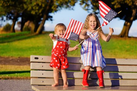 Photo for Group of two happy adorable little kid girls smiling and waving American flag outside, his dress with strip and stars, cowboy hat. Smiling child celebrating 4th july - Independence Day - Royalty Free Image