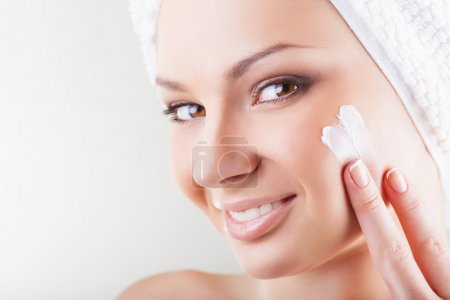 Photo pour Gros plan belle femme appliquant crème cosmétique hydratante sur le visage sur fond clair - image libre de droit