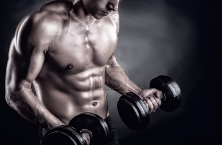 Photo for Closeup of a muscular young man lifting weights on dark background - Royalty Free Image