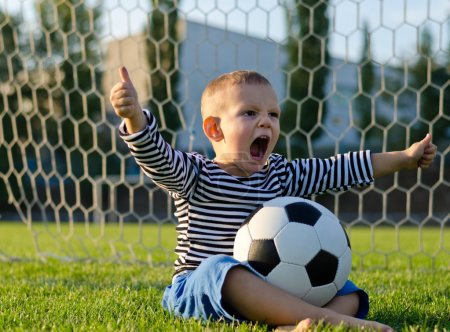 Boy with football shouting with glee
