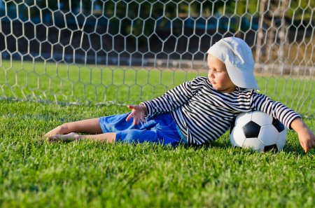 Small boy lying in the goalposts