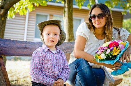 Photo pour Jolie jeune mère assise sur un banc de jardin avec son petit fils le jour de la fête des mères tenant un bouquet coloré de fleurs qu'il vient de lui offrir en cadeau - image libre de droit