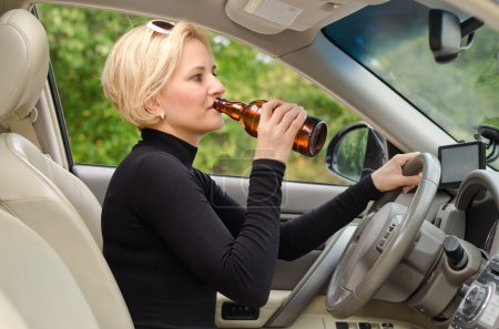 Young female driver drinking and driving