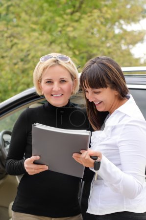Two women signing a contract to buy a car