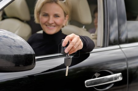Woman driver showing off the keys of a new car