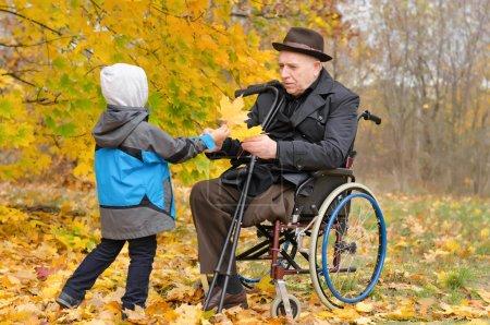 Photo pour Jeune enfant dans une veste chaude hooded donnant une personne âgée handicapée homme assis dans un fauteuil roulant, tenue de béquilles, un tas de coloré jaune l'automne laisse comme ils bénéficient d'un jour à l'automne boisé - image libre de droit