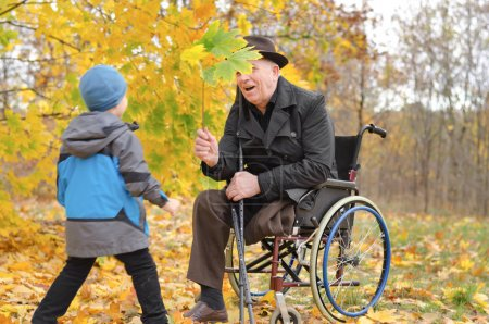 Photo for Young boy playing with his disabled grandfather as the two enjoy a day in the park together amongst the colourful autumn leaves running towards his wheelchair - Royalty Free Image