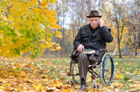 Photo for Elderly disabled man sitting in a wheelchair in a chilly colourful park in autumn with a book on his lap chatting on his mobile phone - Royalty Free Image