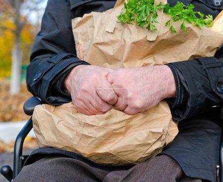 Photo pour Clouse jusqu'à senior homme handicapé faire son épicerie commerçante assis sur la route dans son fauteuil roulant, serrant un grand sac de nourriture et en regardant la caméra - image libre de droit