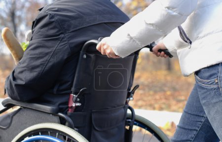Woman pushing a disabled man in a wheelchair