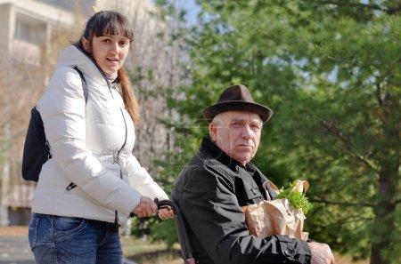 Photo pour Bouchent la vue d'un soignant féminin ou fille aider un vieil homme assis dans un fauteuil roulant lui sortant de faire l'épicerie - image libre de droit