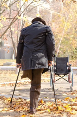 Photo for View from behind of a handicapped one-legged man walking on crutches in an autumn park as he heads for his wheelchair which is parked in the street - Royalty Free Image