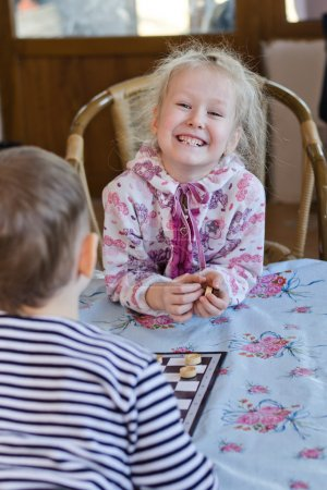 Beautiful laughing little girl playing checkers