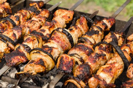 Background of crispy grilled kebabs on a BBQ