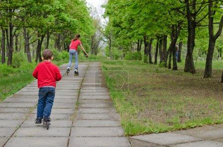 Foto de Niño conduce un scooter a lo largo de un camino pavimentado rural tras una adolescente sobre patines en línea que va a patinar delante de él como los dos disfrutan un poco de ejercicio saludable en un día soleado - Imagen libre de derechos