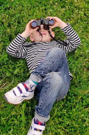 Young boy lying on his back with binoculars