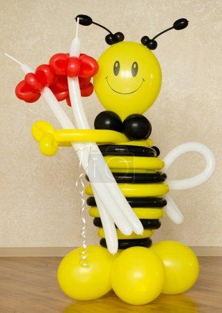 Photo pour Mignon bourdon en plastique jaune et noir coloré avec un bouquet de fleurs rouges et un grand sourire comme cadeau insolite de Saint-Valentin - image libre de droit