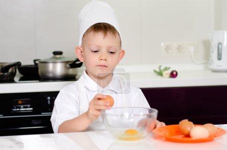 Photo pour Jeune garçon gagnant pour être un chef casser des œufs dans un bol à mélanger avec un regard de concentration comme il suit la recette dans son uniforme de nos chefs - image libre de droit