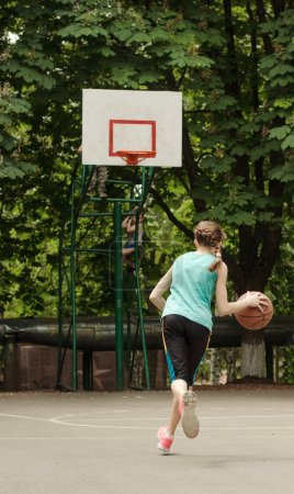 Young girl dribbling a basketball