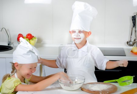 Two cute young children learning to bake