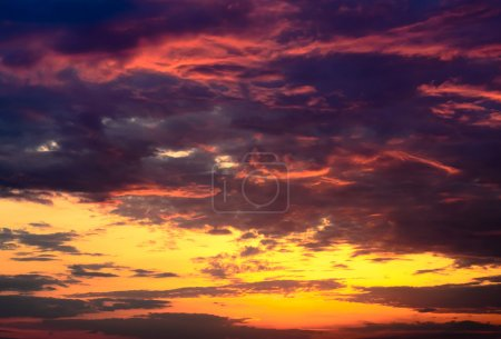 Photo for Celestial background of a dramatic beautiful fiery orange and purple sunset lighting up the cloudsCelestial background of a dramatic beautiful fiery orange and purple sunset lighting up the clouds - Royalty Free Image
