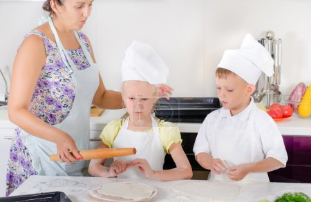Mother teaching two children to bake
