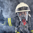 Firewoman in fire protection suit and mask...