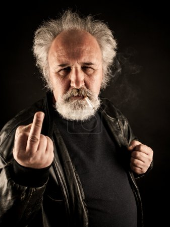 Photo for Grumpy man showing middle finger against black background - Royalty Free Image