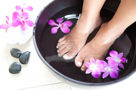Photo for Feminine feet in foot spa bowl with orchids - Royalty Free Image