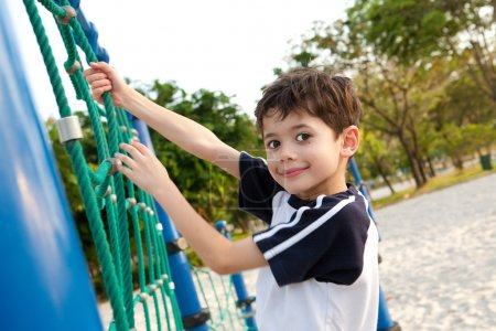Young boy enjoying the playground climbing activity.