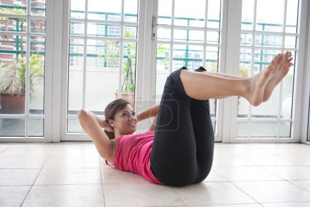 Young fitness woman doing her crunching exercise