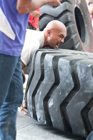 TOA PAYOH, SINGAPORE - MARCH 24 : Contender for Strongman Sulaiman Ismail attempting the six times 350kg tyre flip category in the Strongman Challenge 2012 on March 24, in Toa Payoh Hub, Singapore.