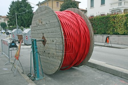 Coils of red high-voltage power cable in the middle of the road