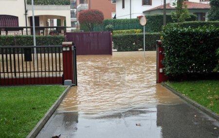Photo pour Entrée d'une maison lors d'une inondation et d'une route complètement inondée - image libre de droit