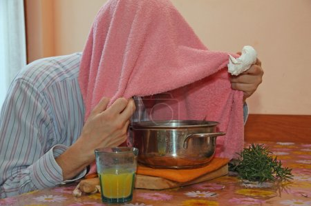 man with pink towel breathe balsam vapors to treat colds and the
