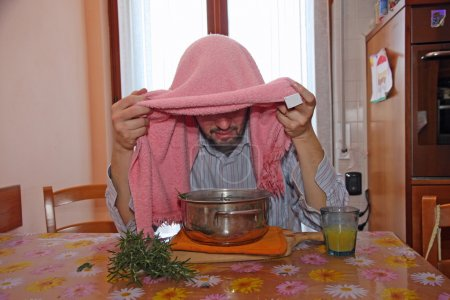 man with pink towel breathe balsam vapors to treat colds