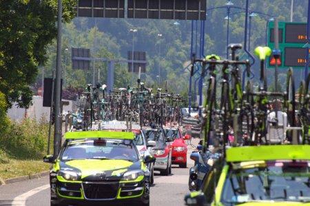 Photo pour Machines puissantes avec des bicyclettes phares Commons suivre les cyclistes pendant la course cycliste dans la rue - image libre de droit
