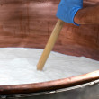 Worker mixes the milk in a large cauldron to make ...