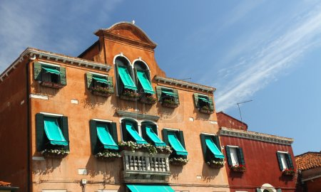 flowery balcony in Venetian style with Windows and green awnings