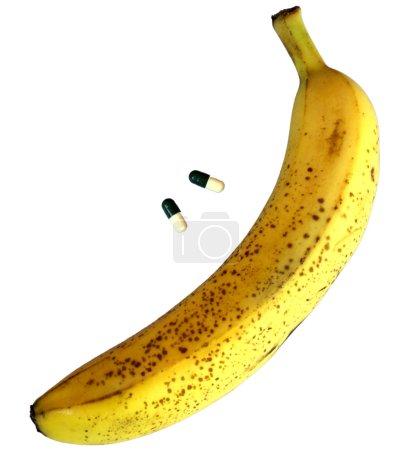 Photo pour Grosse banane jaune avec deux pilules pour les problèmes masculins - image libre de droit