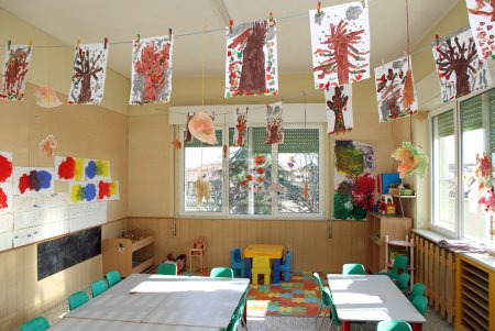 Nursery class of children with many drawings of trees hanging fr