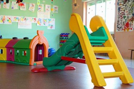 Photo pour Petite glissière et tunnel en plastique dans la maternelle de la salle de jeux - image libre de droit