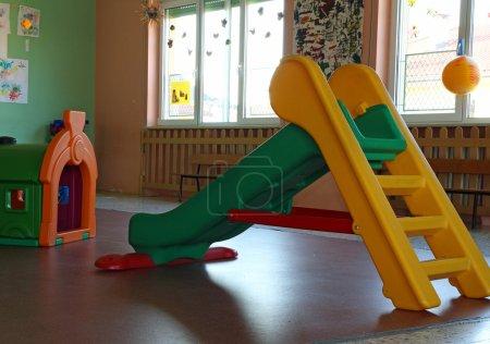 Photo pour Chute en plastique verte et jaune dans la salle de jeux à l'intérieur de la maternelle sans enfants - image libre de droit