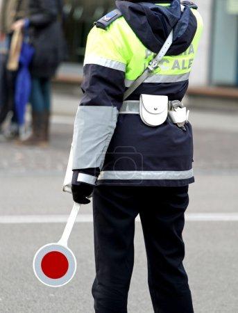 Photo pour Policier avec la pagaie tout en dirigeant la circulation dans la grande ville - image libre de droit