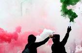 Ultras Fans mit Rauch rot weiß und Grün in schwarz gekleidet