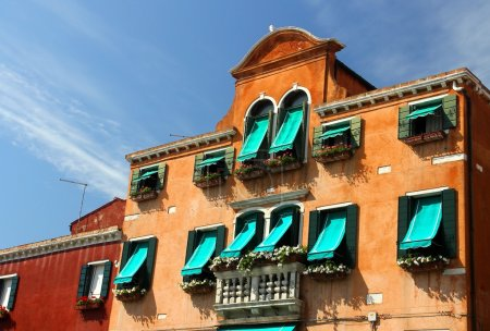 balcony in Venetian style with Windows and green awnings