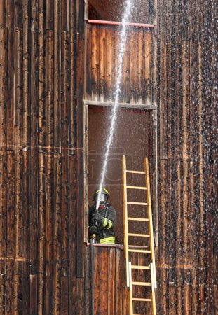 Firefighter with hydrant in action when switching off a fire dur
