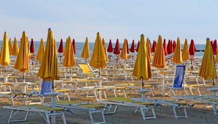 Photo pour Nombreux parasols et transats sur la plage au coucher du soleil sur le bord de mer - image libre de droit